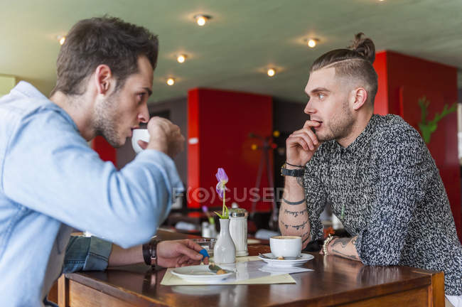 Two men drinking coffee in a cafe — Stock Photo
