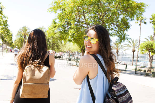 Spain, Barcelona, portrait of smiling woman with sunglasses having a walk with her best friend — Stock Photo