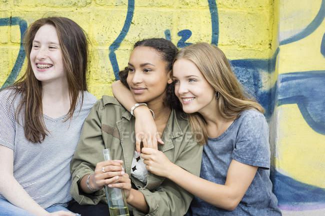 Three teenage girls sitting in front of graffiti — Stock Photo