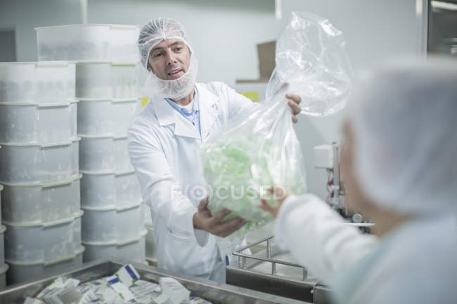 Lab worker in pharmaceutical plant handing over plastic bag — Stock Photo