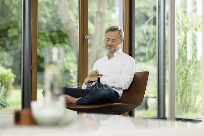 Человек, сидящий на стуле в своей гостиной и смотрящий на умные часы — стоковое фото