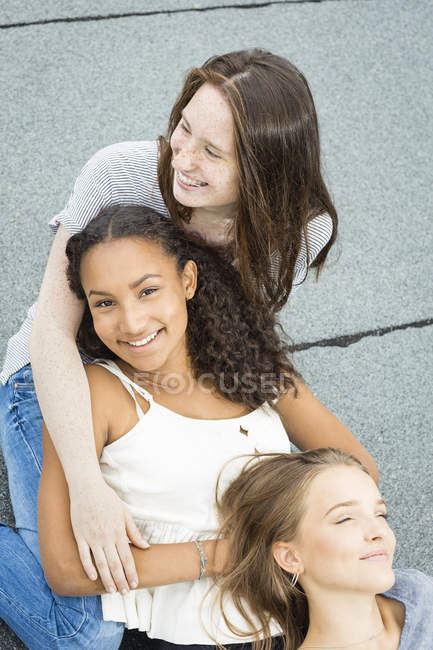Three teenage girls relaxing together on roof top — Stock Photo