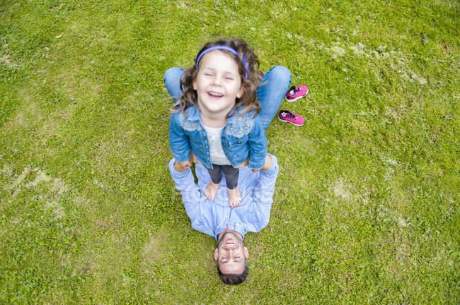 Дочь, стоящая на папе, играющая на лугу в парке, возвышенный вид — стоковое фото