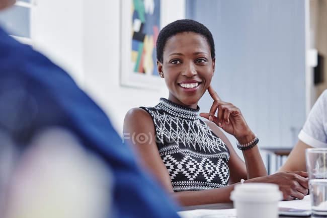 Усміхається жінка на зустрічі, дивлячись на колегу — стокове фото