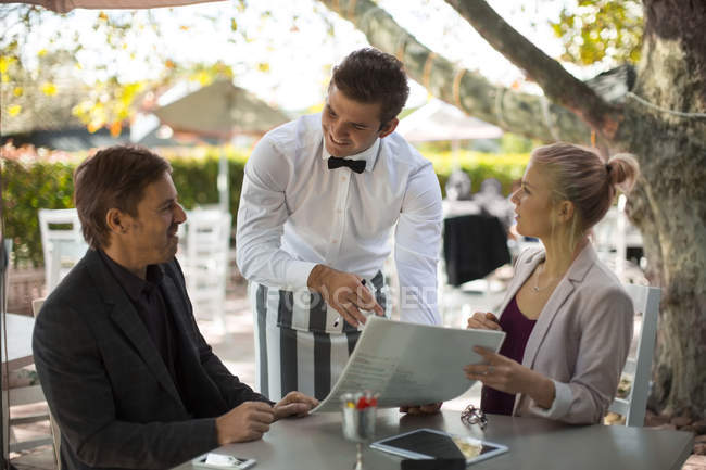 Waiter ready to serve couple seated at outdoor restaraunt — Stock Photo