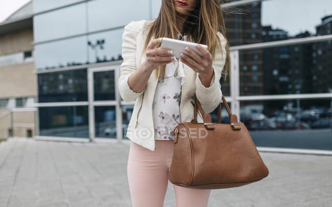 Mujer con tableta digital frente al edificio de oficinas - foto de stock