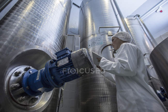 Lab technician in pharmaceutical plant in front of tanks — Stock Photo