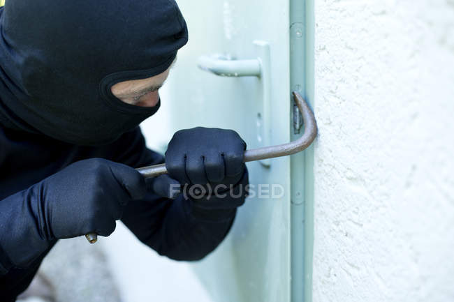 Грабіжник з лом порушення двері в денний час — стокове фото