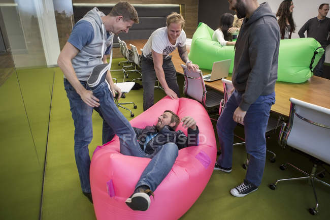 Group of business people playing around with inflatable sofas — Stock Photo