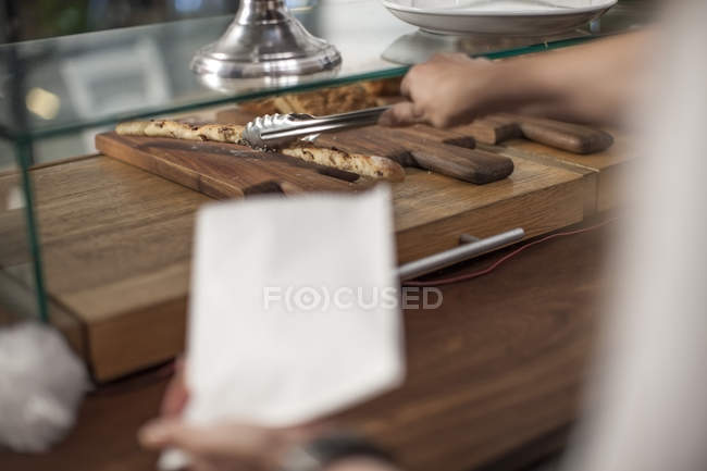 Woman serving roll with pastry tong — Stock Photo