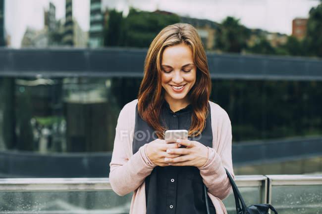 Усміхаючись молоду жінку, за допомогою мобільного телефону на вулиці — стокове фото
