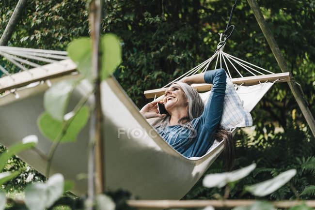 Женщина по телефону отдыхает в гамаке — стоковое фото