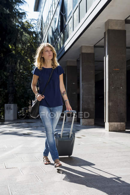 Blond tourist walking with baggage at daytime — Stock Photo