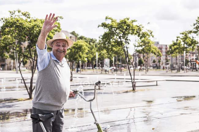 Portrait of waving senior man with folding bicycle — Stock Photo