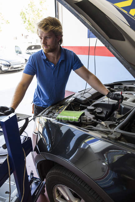 Mécanicien fixer un moteur de voiture tout en utilisant un ordinateur dans son atelier — Photo de stock