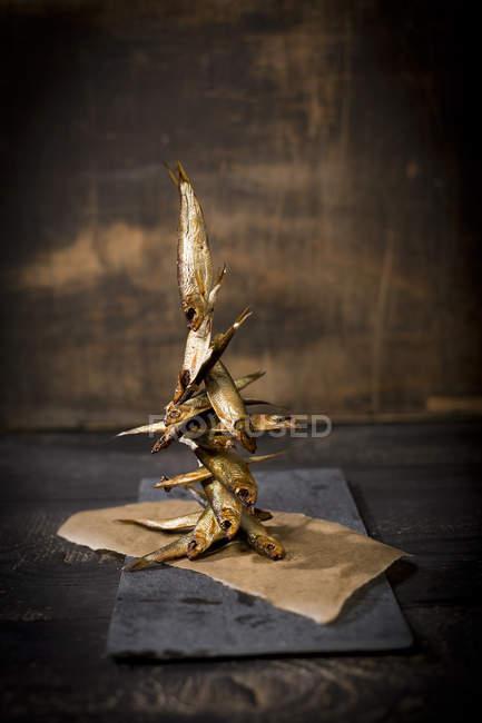 Geräucherte Sprotten auf Backpapier im Haus gestapelt — Stockfoto