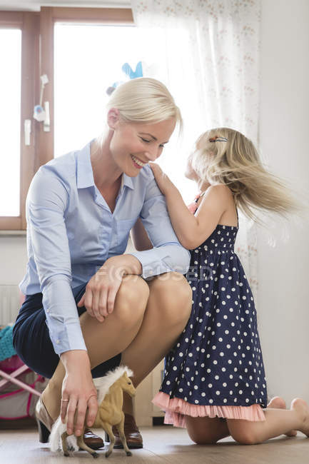 Businesswoman playing with her little daughter — Stock Photo