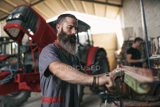 Mechaniker justiert Metallstück in Drehmaschine mit Kollege im Hintergrund — Stockfoto
