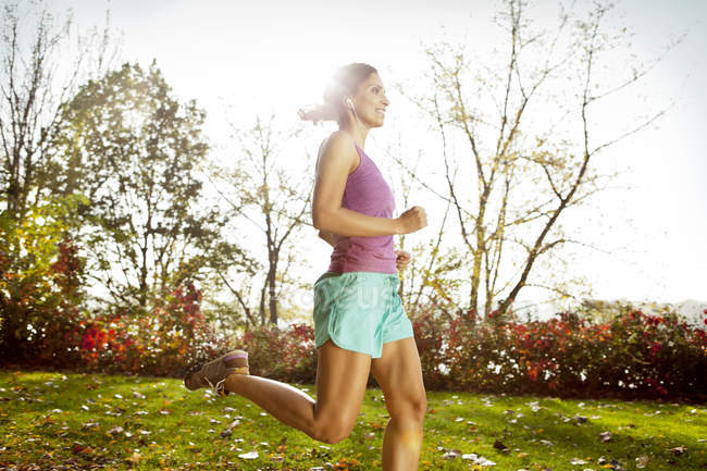 Woman jogging in autumnal park — Stock Photo