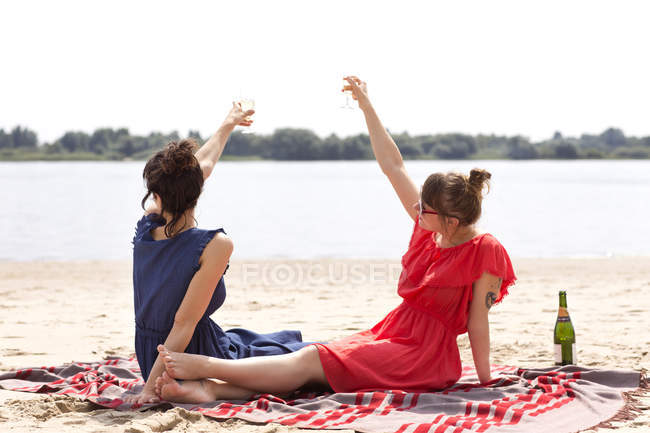Two friends sitting on the beach toasting with glasses of sparkling wine — Stock Photo
