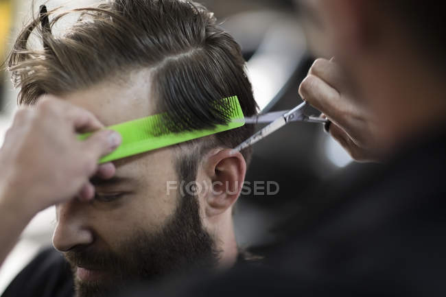 Barber combing and cutting hair of a customer at barbershop — Stock Photo