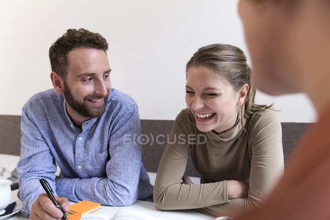 Three smiling friends sitting together taking notes — Stock Photo