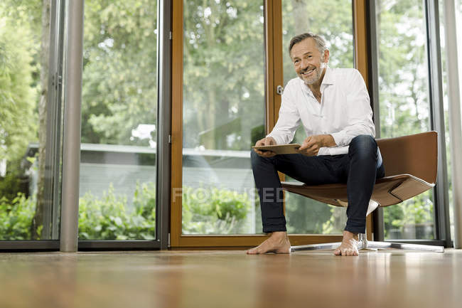 Uomo seduto con tablet sulla sedia nel suo salotto — Foto stock