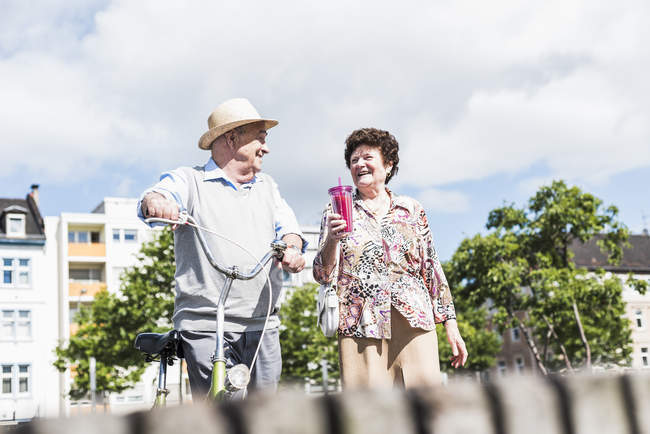 Senior couple with bicycle walking in city — Stock Photo