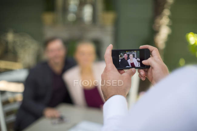 Mann, die Smartphone-Aufnahme des Paares im Restaurant unter freiem Himmel — Stockfoto