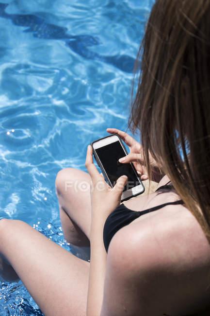 Женщина, сидя на краю бассейна, освежающий с ее ноги в воду с помощью ее телефон, частичным видом — стоковое фото