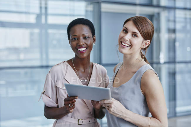 Duas mulheres de negócios com tablet digital no escritório moderno — Fotografia de Stock