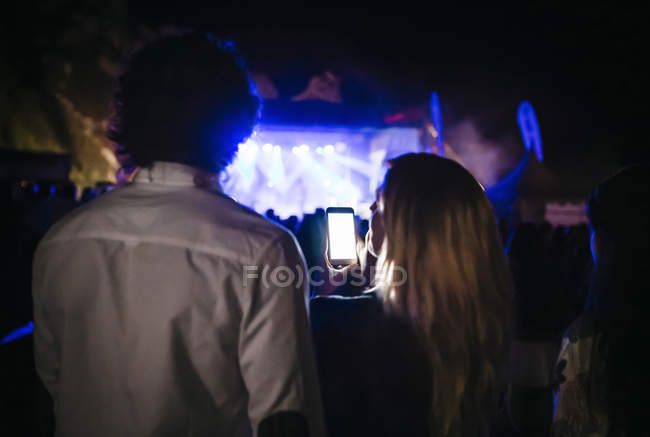 Back view of young woman taking pictures with smartphone at summer concert — Stock Photo