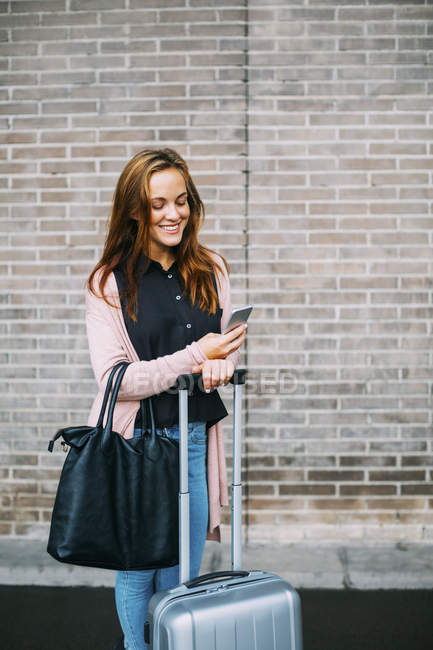 Smiling woman with baggage using cell phone — Stock Photo