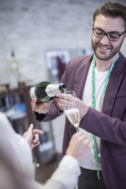 Модельєр розливу в стакан шампанське — стокове фото