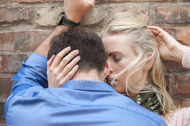 Sensual couple in love leaning against brick wall — Stock Photo