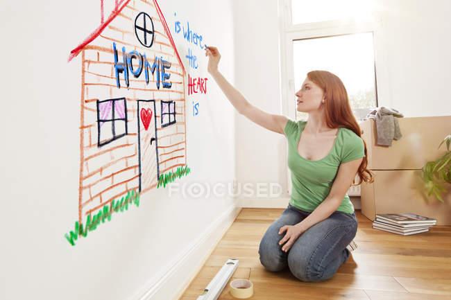 Giovane donna che disegna una casa su un muro in un nuovo appartamento — Foto stock