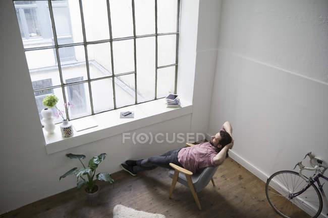 Uomo che si siede nella sedia e sognare ad occhi aperti in edificio moderno — Foto stock