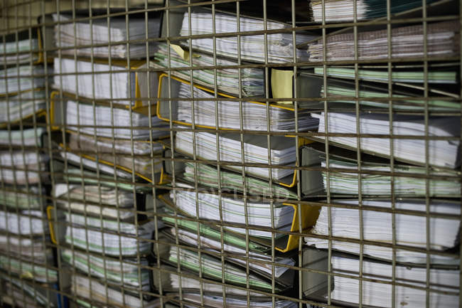 Pile of office files behind grid — Stock Photo