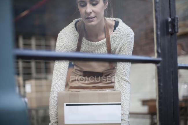 Woman picking up cardboard box — Stock Photo