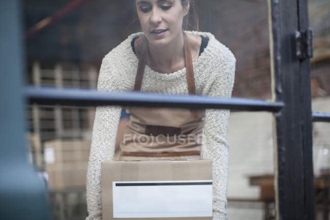 Woman picking up cardboard box — Stock Photo