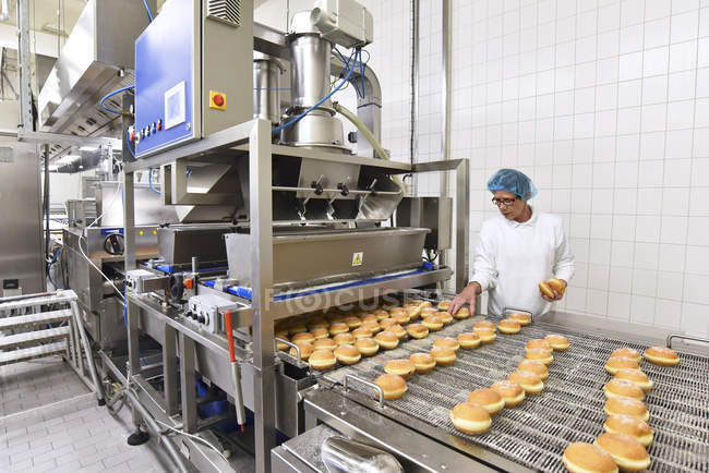 Worker at production line in a baking factory with Berliners — Stock Photo