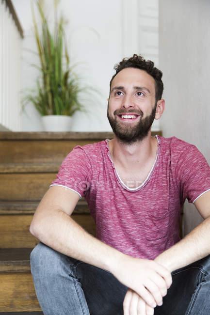 Lächelnder junger Mann sitzt auf der Treppe — Stockfoto