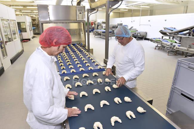 Працівників, що працюють на лінії виробництва в випічки фабрика з круасани — стокове фото
