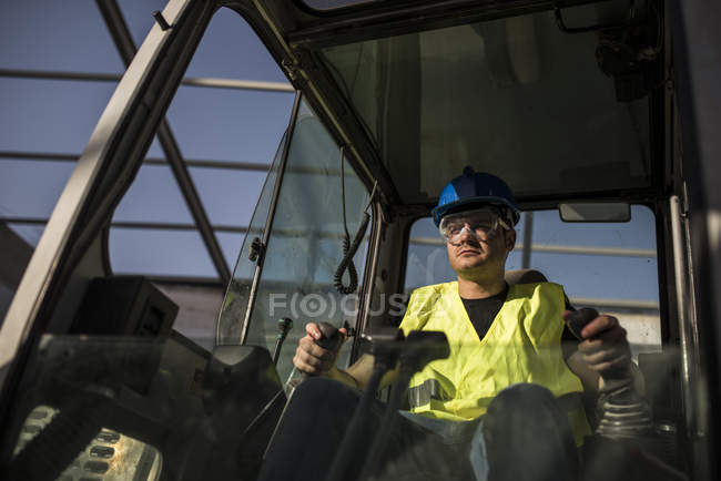 Construction worker working in caterpillar — Stock Photo