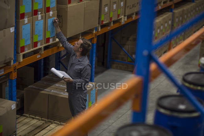 Worker taking stock in warehouse — Stock Photo