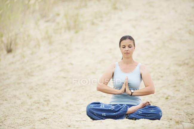 Mulher com olhos fechados relaxantes em posição de lótus na areia — Fotografia de Stock