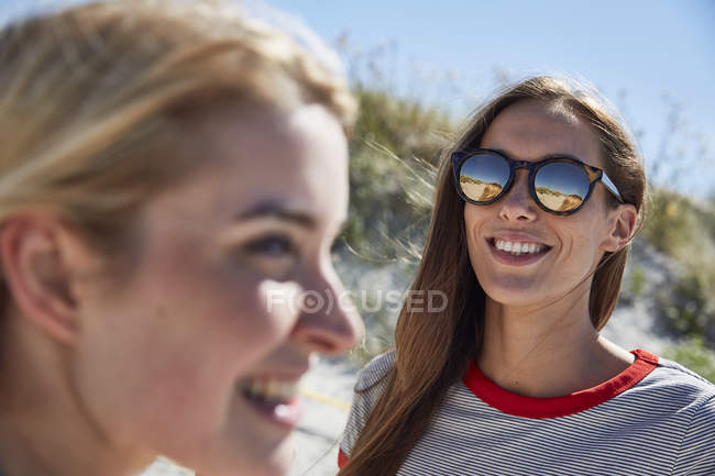 Smiling young woman wearing sunglasses on the beach — Stock Photo