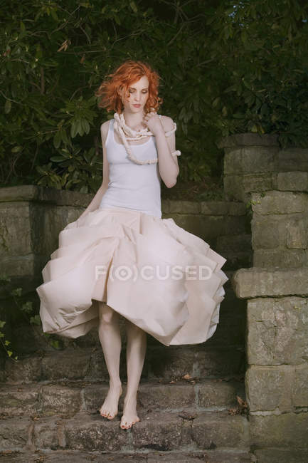 Redheaded young woman in fancy dress walking barefeet on stairs — Stock Photo