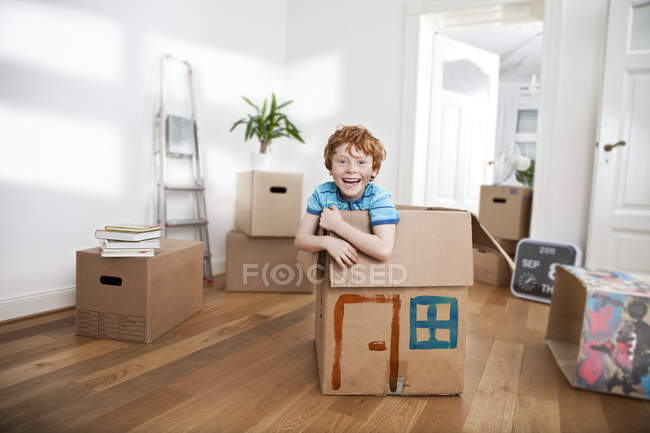 Happy boy looking out of a cardboard box in new apartment — Stock Photo
