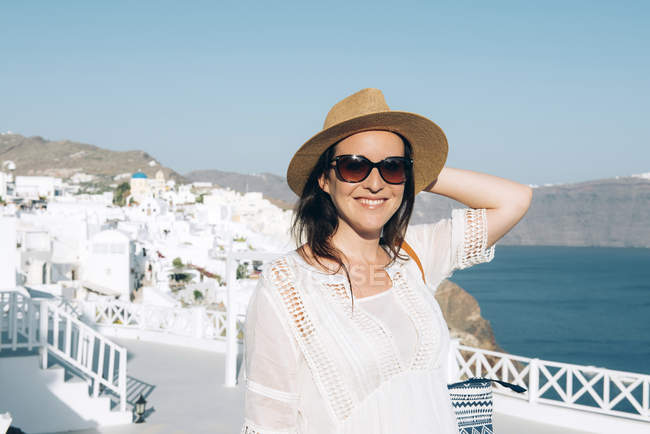 Greece, Santorini, Oia, smiling woman wearing sunglasses and straw hat — Stock Photo